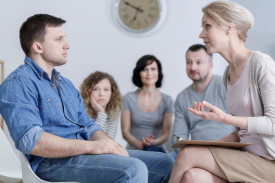 man sitting in group therapy and listening to the psychologist